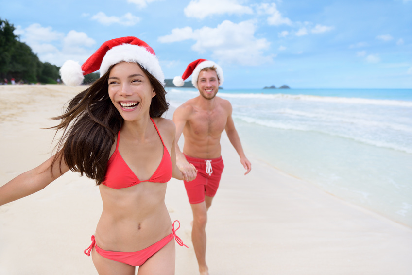 Happy Christmas couple having fun running on beach. Beautiful young Asian woman and Caucasian boyfriend holding hands playing on sand during winter travel holidays wearing santa hats.